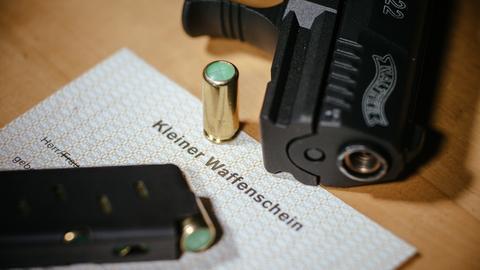 """Ein Kleiner Waffenschein liegt zwischen einer Schreckschuss-Pistole """"Walther P22"""", einem Magazin und einer Knallpatrone."""