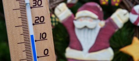Ein Thermometer neben einem Weihnachtsmann zeigt 14 Grad