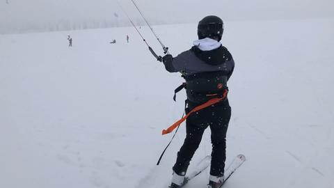Ein Skifahrer lässt sich von einem Lift die Wasserkuppe hochziehen.