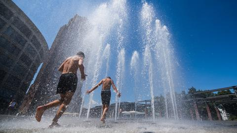 Jugendliche springen durch Fontänen eines Brunnens