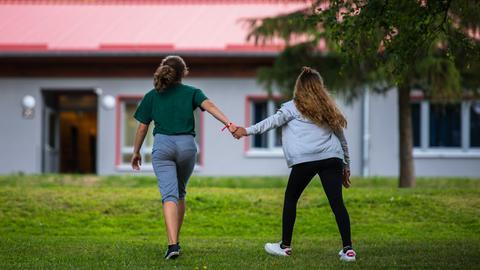 Zwei Mädchen laufen Hand in Hand vor einem Wohnhaus im Schullandheim Wegscheide in Bad Orb.