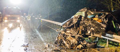 Zerstörtes Auto am Straßenrand und Rettungskräfte