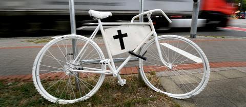 Ein weißes Fahrrad mit schwarzem Kreuz erinnert an einen Unfall mit tödlichem Ausgang.
