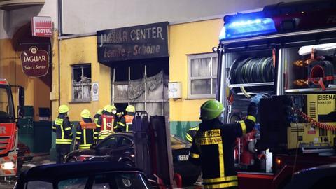 Feuerwehrauto und Feuerwehrmänner vor beschädigtem Werkstatteingang.