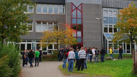 Außenansicht des Schulgebäudes mit mehreren Schülern davor.
