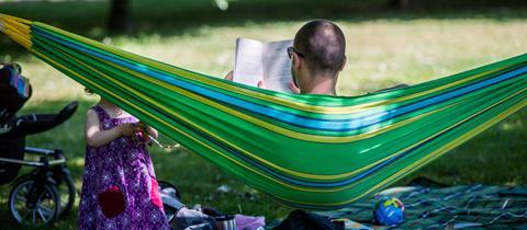 Ein Mann sitzt bei Sonnenschein in einer Hängematte und liest ein Buch, davor spielt sein Kind auf einer Decke.