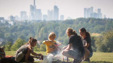 Eine Familie grillt vor der Frankfurter Skyline.