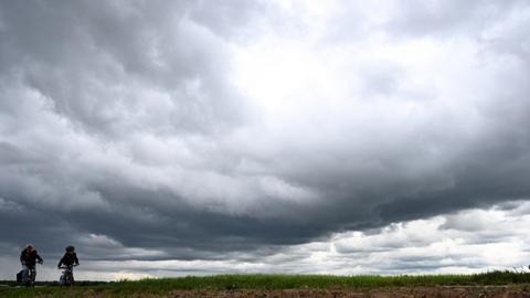 Ein Erwachsener und ein Kind auf Fahrrädern fahren durch Felder - über ihnen türmen sich Gewitterwolken auf.