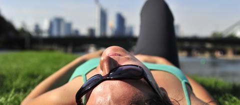 Frau auf einer Wiese vor der Frankfurter Skyline