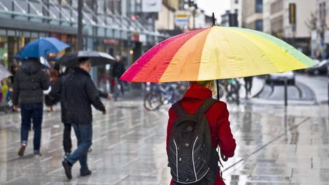 """Die Einkaufsstraße """"Zeil"""" in Frankfurt bei Regenwetter. Im Vordergrund eine Frau mit einem großen Regenschirm in Regenbogenfarben."""