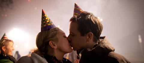 Ein küssendes Paar vor nebligem Feuerwerk.