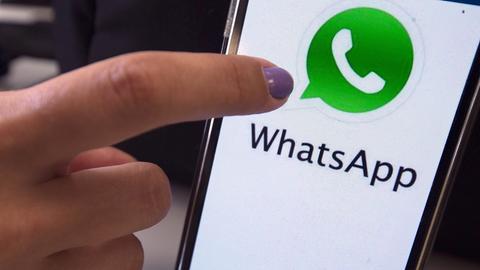 Finger, der auf einem Smartphone WhatsApp aufruft.