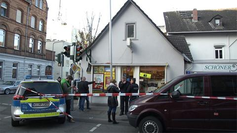 Der Kiosk von vorne, daneben ein Polizeiwagen und ein Transporter.