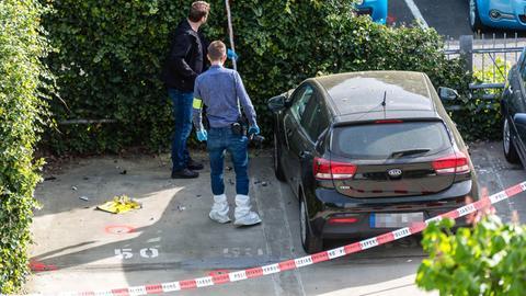 Polizeibeamte untersuchen den Ort, wo es zuvor auf einem Auto eine Explosion gegeben hatte.