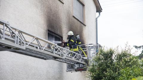 Ein Feuerwehrmann löscht das Feuer in einer Wohnung in Wiesbaden.