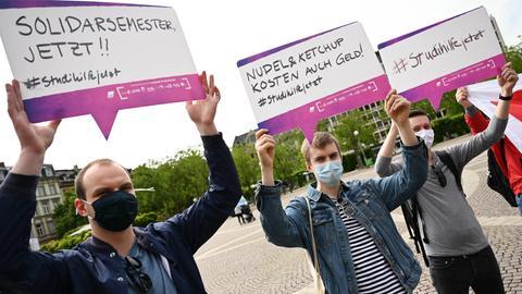 Drei Studenten halten bei einer Demo in Wiesbaden für finanzielle Unterstützung während der Corona-Krise Plakate hoch