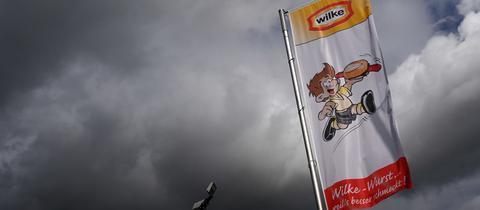Dunkle Wolken türmen sich hinter einer Werbefahne des Fleischherstellers Wilke Wurstwaren