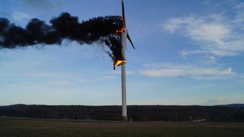 Ein brennendes Teil der Verkleidung des Windrads fällt zu Boden.