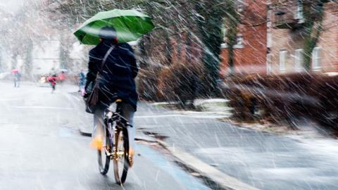 Fahrradfahrer bei Schneeregen mit Schirm in der Hand
