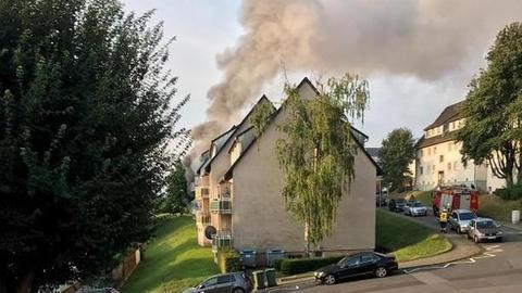 Qualmender Rauch steigt aus einem Mehrfamilienhaus in die Luft.