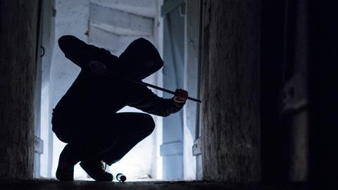 Ein Einbrecher hebelt mit einem Brecheisen eine Tür im Keller eines Hauses auf. (Symbolbild)