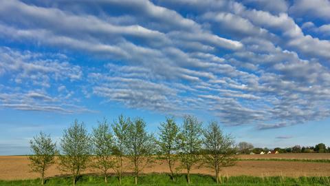 Wolken ziehen im Mai über ein Feld hinweg