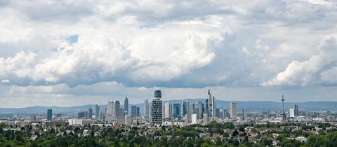 Frankfurt aus der Ferne fotografiert. Dicke Quellwolken ziehen über die Stadt und berühren fast die umliegende Landschaft.