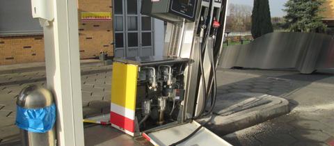 Die Zapfsäule steht schief, vor ihr auf dem Boden ist Benzin ausgelaufen.