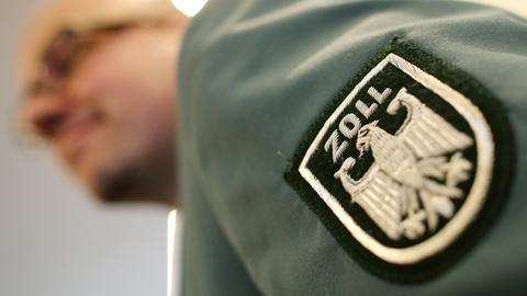 Nahaufnahme: der linke Ärmel eines Zollbeamten mit dem aufgenähten Zoll-Wappen