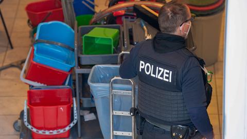 Ein Polizist bei einer Razzia in einer Reinigungsfirma