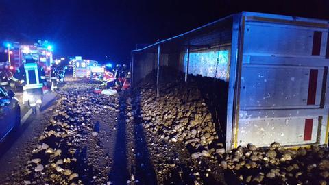 Bei Nacht liegt ein umgekippter Container auf der Autobahn, um den herum Unmengen Zuckerrüben liegen. Feuerwehrleute und Rettungswagen stehen dabei.