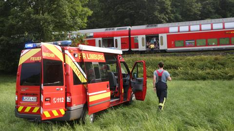 Ein Regionalzug steht bei Niederbrechen auf freier Strecke. Feuerwehrleute betreuen die Passagiere.