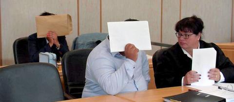 Die Angeklagten verdecken ihre Gesichter, Anwältin