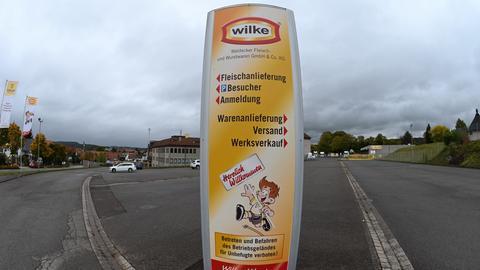 Das Gelände der Wilke Wurstwaren, man sieht einen großen Werbeaufsteller mit dem Firmenlogo, im Hintergrund parken Fahrzeuge.