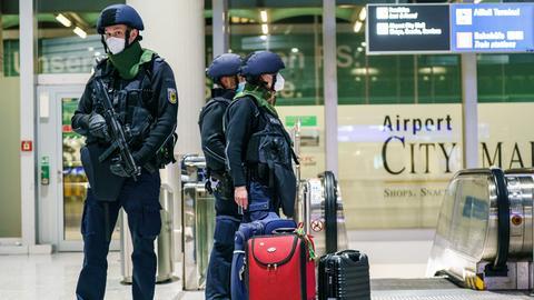 Ein Polizist steht im Terminal 1 neben mehreren Gepäckstücken.