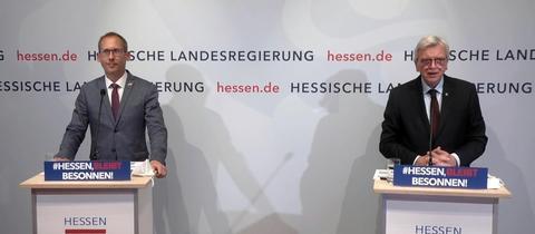 Gesundheitsminister Kai Klose und Ministerpräsident Volker Bouffier) stehen nebeneinander an Stehpulten. Im Hintergrund eine Wand mit den Schriftzügen und Logos der hessischen Landesregierung.