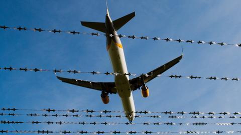 Ein Flugzeug fliegt über Stacheldraht