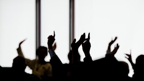 Hände in der Höhe bei einer politischen Abstimmung