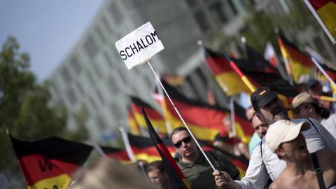"""AfD-Anhänger bei einer Kundgebung, einer trägt ein Schild mit der Aufschrift """"Schalom"""""""
