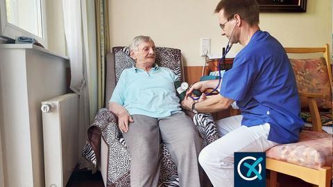 Altenpfleger Torsten Birkholz misst Blutdruck bei einer Bewohnerin, die in einem gemusterten Sessel am Fenster sitzt.