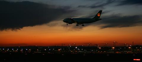Flugzeug fliegt nachts auf Flughafen Frankfurt zu
