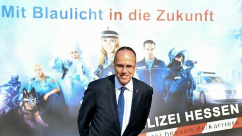 Peter Beuth vor einem Polizei-Plakat.