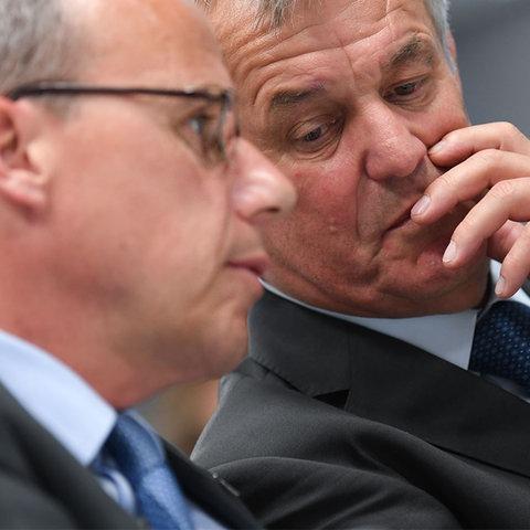 Foto: Peter Beuth (Innenminister) und Gerhard Bereswill (Polizeipräsident) stecken nebeneinander sitzend die Köpfe zusammen und flüstern.
