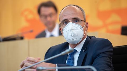 Innenminister Peter Beuth sitzt mit Maske im Landtag.