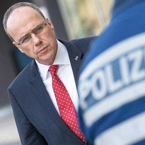 """Innenminister Peter Beuth. So fotografiert, dass er auf den Rücken eines Polizeibeamten zu schauen scheint, auf dessen Rücken """"Polizei"""" steht."""