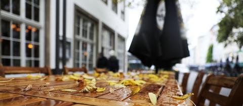 Herbstlaub liegt auf verwaisten Tischen der Außengastronomie
