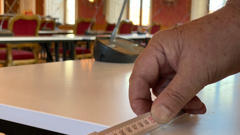 Beim Aufbau der Tische für die Bischofskonferenz wird der Corona-Abstand abgemessen