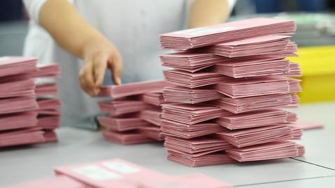 Auf einem Tisch liegen ordentlich gestapelt viele rote Briefwahlumschläge.
