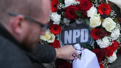 Mit einem Trauerkranz protestiert die Partei Die Partei auf einer Kundgebung gegen die NPD.