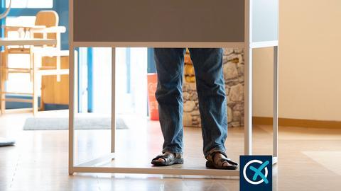 Ein Mann steht in einer Wahlkabine und füllt seinen Stimmzettel aus. Nur seine Beine sind zu sehen, die unter dem abgeschirmten Wahltisch hervorschauen.